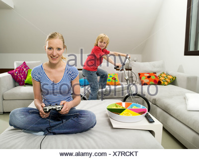 Mother and son in living room, mother playing computre game - Stock Photo