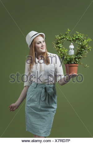 Woman holding a flower pot with a light bulb - Stock Photo
