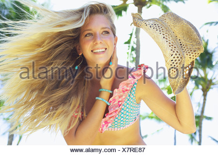 Portrait Of A Teenage Girl In A Bikini With Windblown Hair Holding A Hat;Maui Hawaii United States Of America - Stock Photo