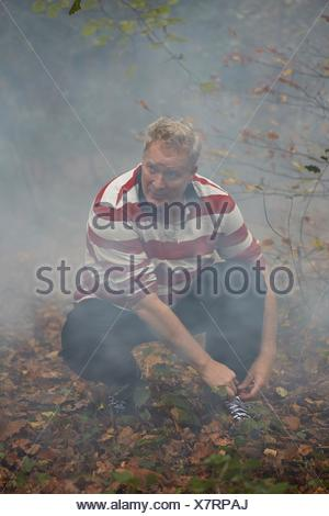 Mature male runner crouching to tie trainer laces in misty forest - Stock Photo