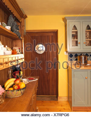 Dark wood door and wooden dresser in yellow nineties kitchen with pale gray fitted cupboards - Stock Photo