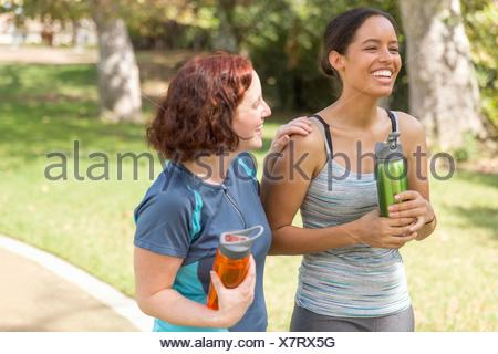 High angle view of young women out walking wearing sports clothing carrying water bottles smiling - Stock Photo
