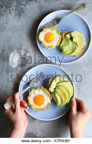 Baked eggs in potato nests with avocado toast - Stock Photo