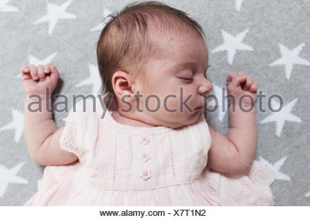 Baby girl sleeping on blanket - Stock Photo