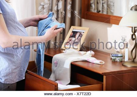 Pregnant woman holding baby clothes, mid section - Stock Photo