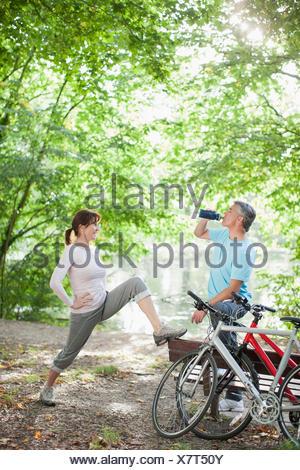 Couple stretching before exercise near lake - Stock Photo