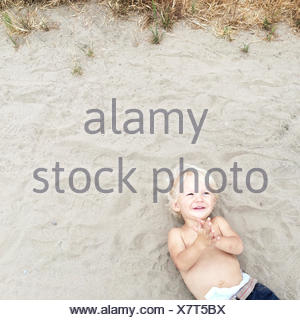 Overhead view of boy lying on beach - Stock Photo