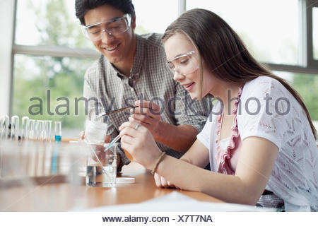 teacher assisting students in chemistry class - Stock Photo