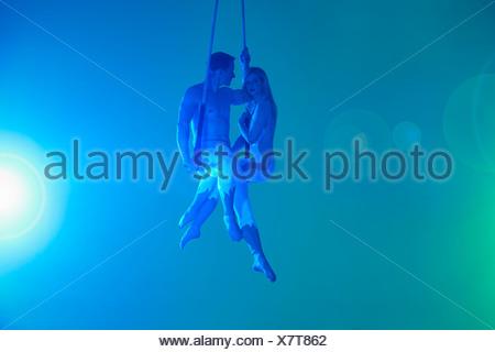 Couple sitting on trapeze - Stock Photo