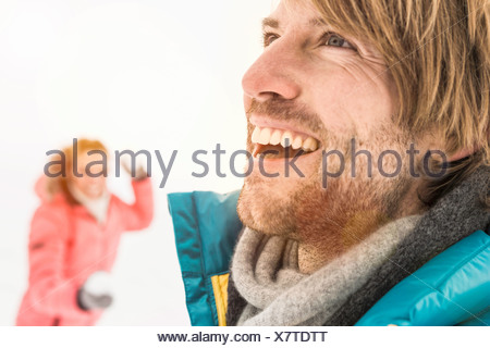 Man laughing, woman throwing snowball in background - Stock Photo