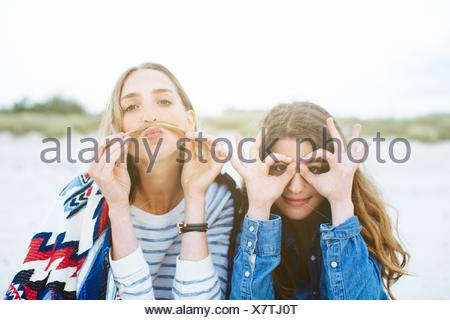 Portrait of two young female friends making moustache and spectacled faces on beach - Stock Photo