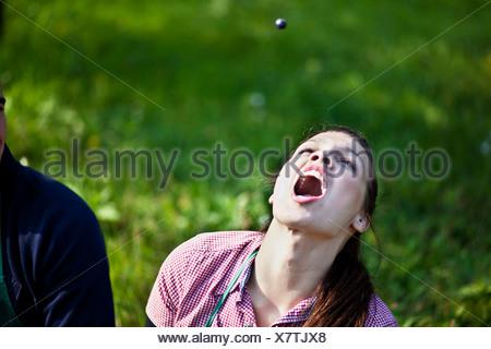 Croatia, Baranja, Young woman catching a grape with mouth open - Stock Photo