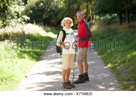 A mature couple standing on a country path, smiling - Stock Photo
