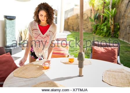 Young woman laying placemats on patio table - Stock Photo