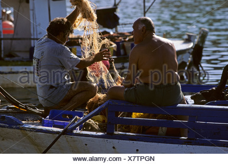 Two fishermen with their fish nets in the harbour of Agios Georgios on the Akamas Peninsula, Cyprus - Stock Photo
