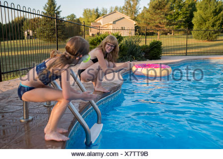 ... Mother And Daughter On Edge Of Swimming Pool, Ready To Dive In   Stock  Photo