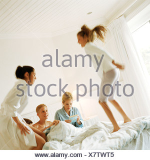 Young people on bed, playing around - Stock Photo