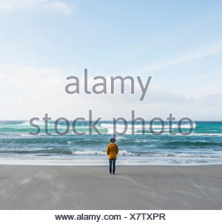 Lonely person standing by the sea, looking out into the distance, Sandfly Bay, Dunedin, Otago, South Island, New Zealand - Stock Photo