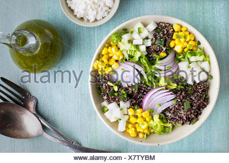 Roasted Poblano Quinoa Salad served with queso fresco, cilantro dressing. Photographed on a light blue/green background from top - Stock Photo