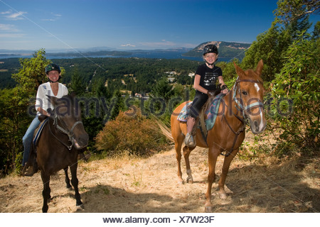 Horseback riding is a popular activity on Vancouver Island  near Duncan, Southern Gulf Islands and Mount Baker in far distance - Stock Photo