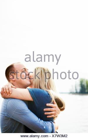Sweden, Gastrikland, Sandviken, Smiling couple hugging with lake in background - Stock Photo