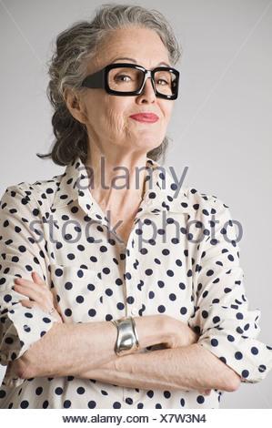 Portrait of senior woman, arms crossed - Stock Photo