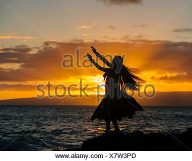 Silhouetted young woman in traditional costume, hula dancing on coastal rock at sunset, Maui, Hawaii, USA - Stock Photo