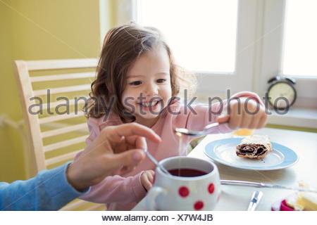 Portrait of little girl giving honey at her mother's tea - Stock Photo