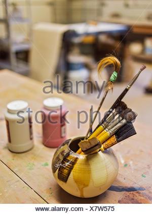 Brushes in bowl in art studio - Stock Photo