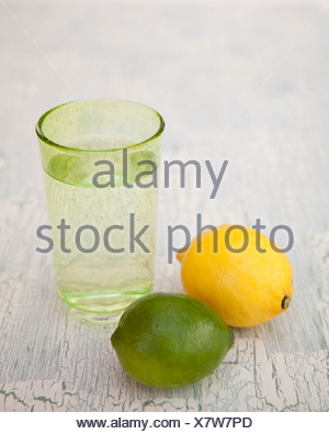 Glass of sparkling water with lemon and lime - Stock Photo