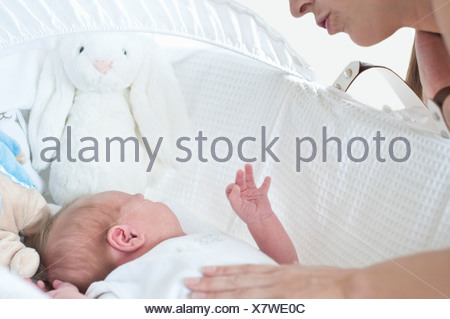 Mother comforting infant son in crib - Stock Photo