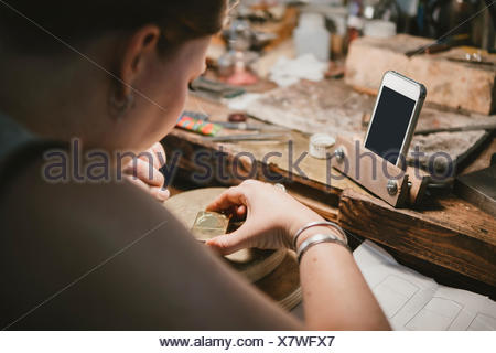 Over shoulder view of female jeweller engraving metal at workbench - Stock Photo