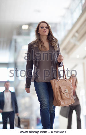 Young businesswoman walking along conference centre corridor - Stock Photo