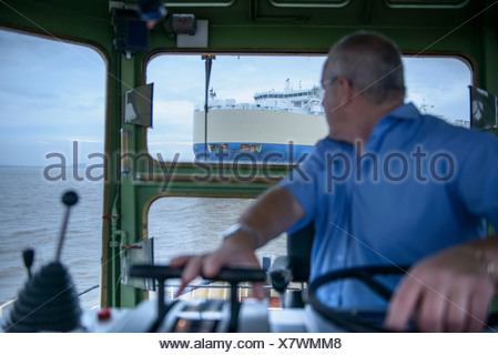 Tugboat towing ship to harbor - Stock Photo