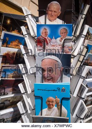 A postcard stand in Saint Peter's Square with postcards of Pope John Paul II and Pope Francis - Stock Photo