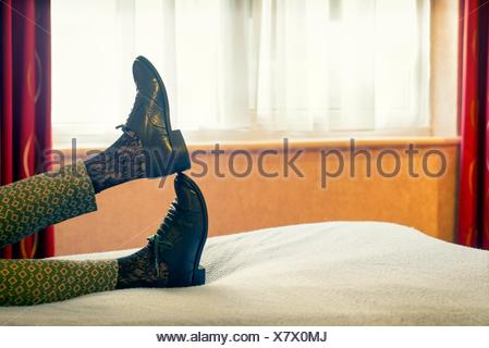 Closeup of feet of woman with oxford shoes lying on a bed in a relaxing position and a window in the background. - Stock Photo