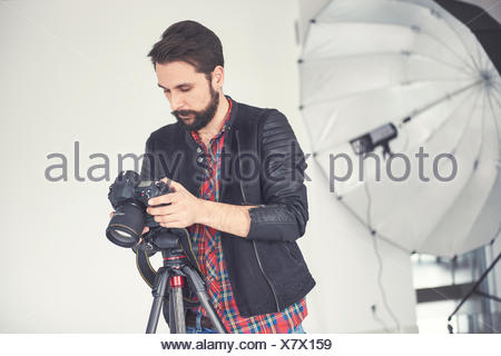 Male photographer reviewing studio photo shoot on digital slr - Stock Photo