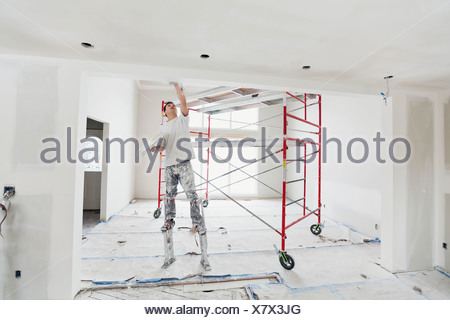 Tradesman on stilts plastering drywall in home - Stock Photo