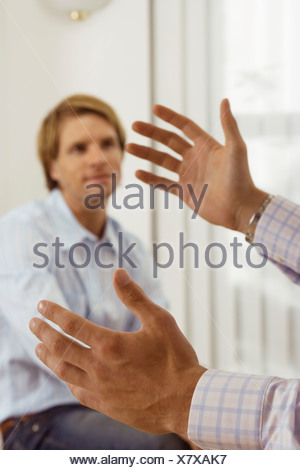 Two businessmen talking in office focus on man gesturing with hands in foreground - Stock Photo