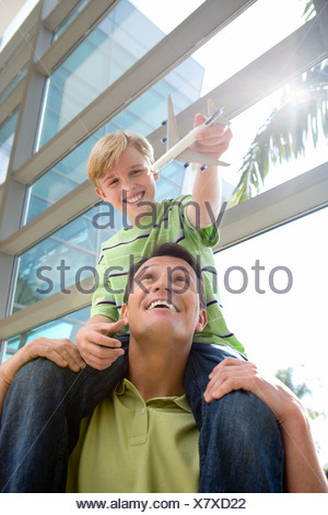 Father carrying son  on shoulders in airport, boy holding toy aeroplane, smiling, front view, low angle view lens flare - Stock Photo