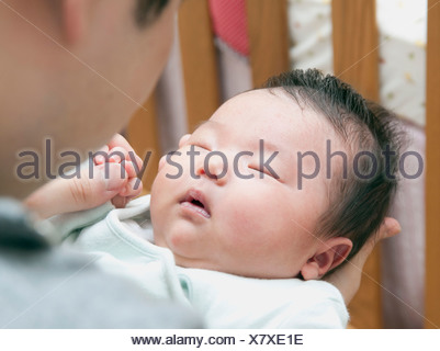 Father holding sleeping baby - Stock Photo