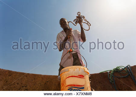 man fetching water from a well in the sahel region of the Senegal river, Senegal - Stock Photo
