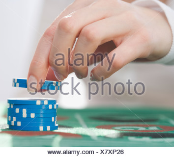 Woman picking up poker chips - Stock Photo