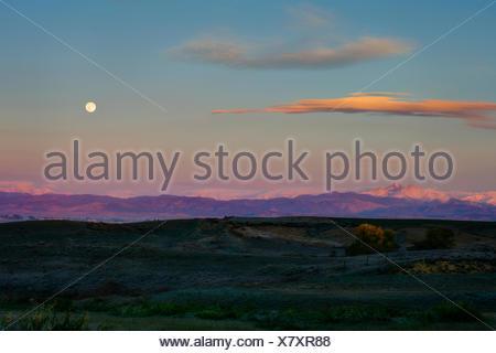 Moon setting and sunrise over rockey mountains - Stock Photo