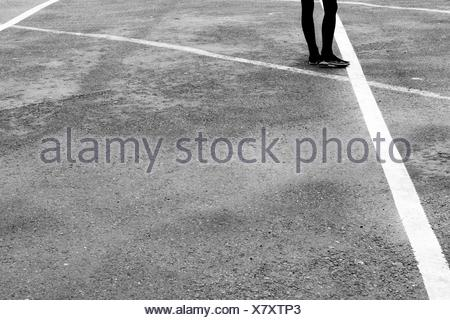 Low Section Of Woman Standing On Road - Stock Photo