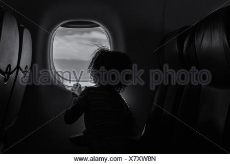 Rear view of a girl looking out of the window on a plane - Stock Photo