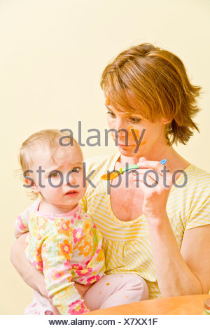 Frustrated mother trying to feed messy baby - Stock Photo