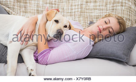 Beautiful blonde on couch with pet dog - Stock Photo