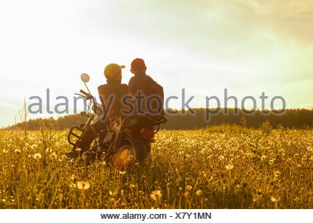 Two young boys, sitting on motorbike, in field, rear view - Stock Photo