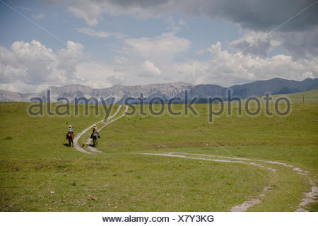 Ranchers horseback riding along winding path rural landscape - Stock Photo